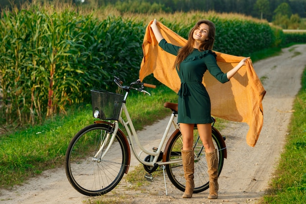 Femme à Vélo Par La Route De Campagne Dans Le Champ De Maïs Photo Premium