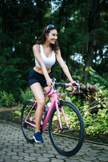 Femme, vélo route, dans parc portrait de belle jeune femme en vélo rose. Photo gratuit