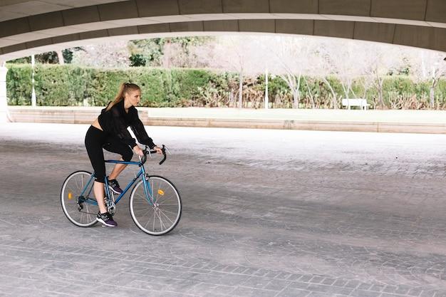Femme à vélo sous le pont Photo gratuit