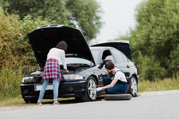 Femme vérifiant le moteur et l'homme change de pneu Photo gratuit