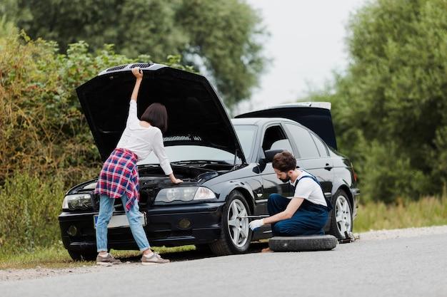 Femme vérifiant le moteur et l'homme échangeant un pneu Photo gratuit