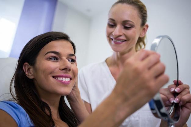 Femme Vérifiant Sa Peau Dans Le Miroir Après Avoir Reçu Un Traitement Cosmétique Photo gratuit