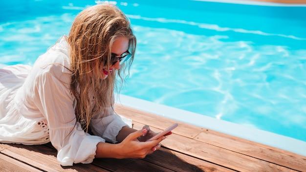 Femme vérifiant son téléphone à la piscine Photo gratuit