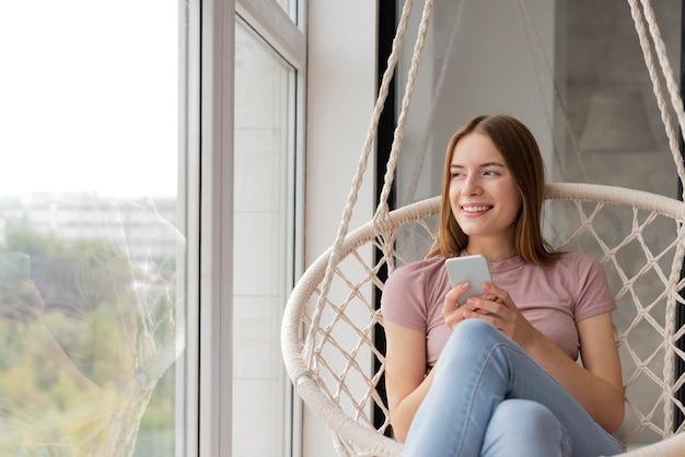 Femme vérifiant son téléphone et regardant par la fenêtre Photo gratuit