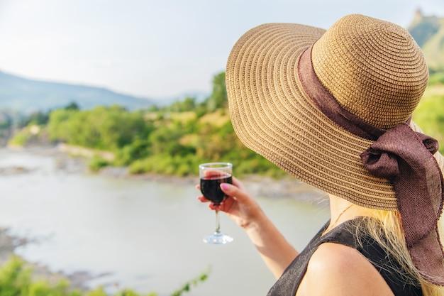 Femme avec un verre de vin sur fond de montagnes de géorgie Photo Premium