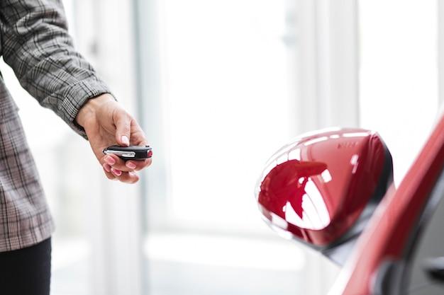 Femme verrouillant la voiture de la clé Photo gratuit