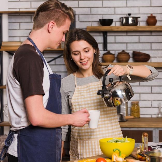 Femme versant de l'eau de la bouilloire dans une tasse pour homme Photo gratuit