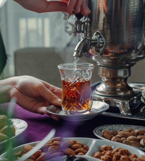Femme versant de l'eau chaude dans un verre avec du thé noir de samovar Photo gratuit