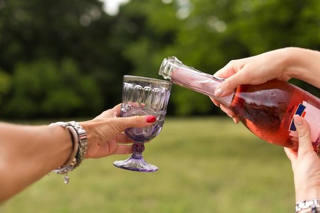 Femme verse du champagne dans des verres au pique-nique. Photo Premium