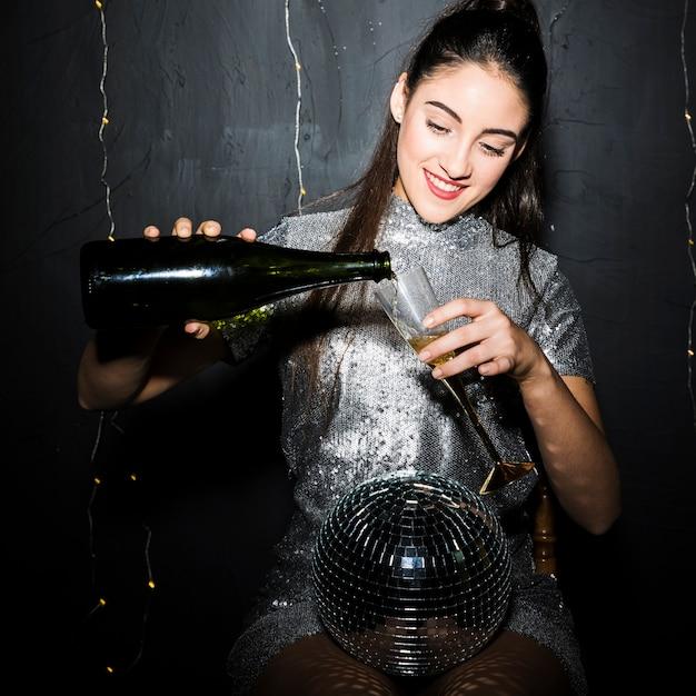Femme, verser, champagne, dans, verre, près, disco ball Photo gratuit