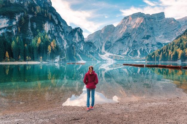 Femme En Veste Rouge Est Debout Sur La Côte Du Lac Braies Au Lever Du Soleil En Automne. Dolomites, Italie. Photo Premium