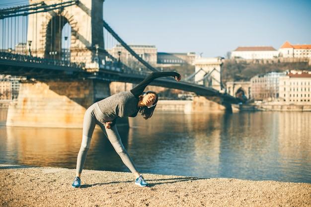 Femme en vêtements de sport s'étirant sur la promenade du danube à budapest Photo Premium