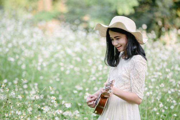 Femme vêtue d'une jolie robe blanche et jouant du ukulélé Photo gratuit