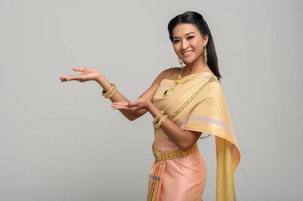 Femme vêtue d'une robe thaïlandaise faite d'un symbole de la main Photo gratuit