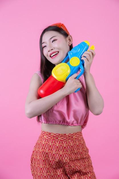 Une femme vêtue d'un vêtement traditionnel thaïlandais tenant un pistolet à eau sur un fond rose. Photo gratuit