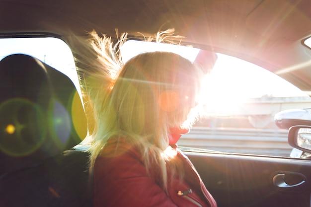 Femme en voiture regardant par la fenêtre Photo gratuit