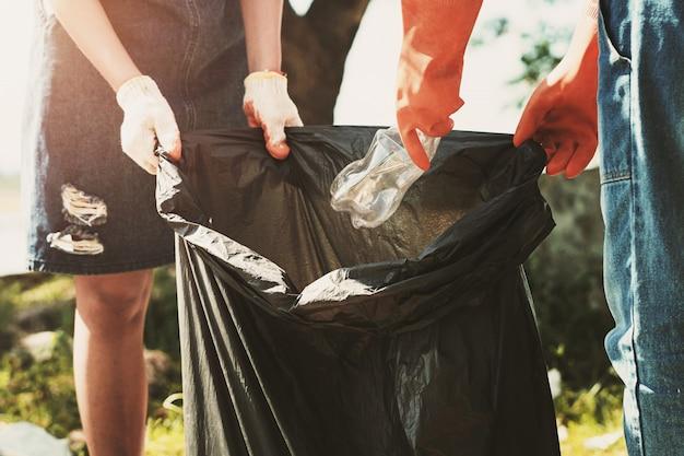 Femme volontaire ramasser des ordures en plastique pour le nettoyage au parc de la rivière Photo Premium