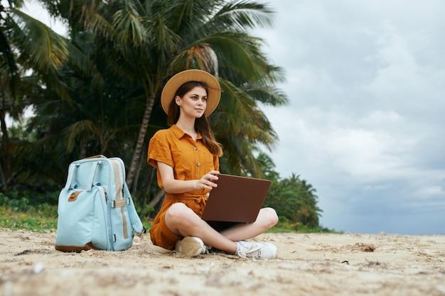 Une Femme Voyage Avec Un Ordinateur Portable Le Long De L'océan Le Long Du Sable Avec Des Palmiers Photo Premium