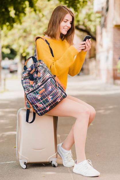 Femme voyageant seule vérifiant son téléphone Photo gratuit