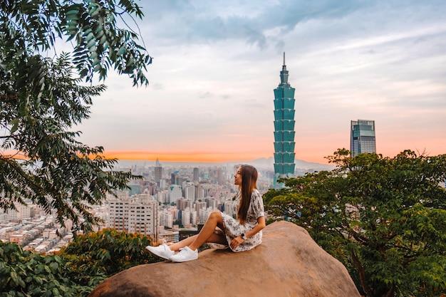 Femme de voyageur et coucher de soleil avec vue sur les toits de la ville de taipei taipei 101 bâtiment de la ville financière de taipei, taiwan Photo Premium