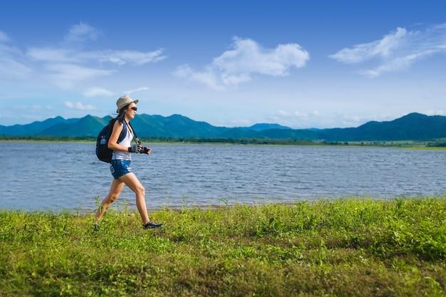 Femme voyageur debout près du lac dans la montagne Photo Premium