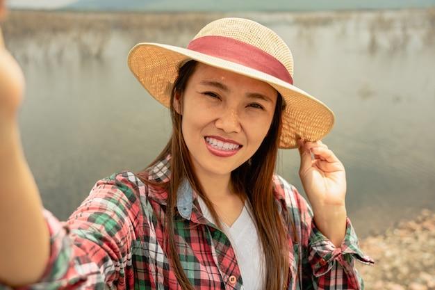 Femme de voyageur prenant selfie au bord du lac en été. Photo Premium