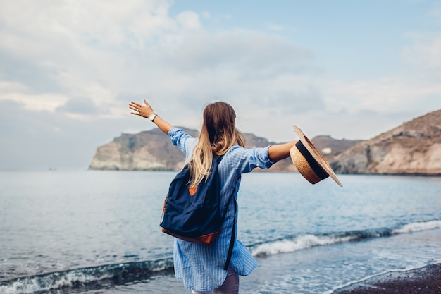 Femme De Voyageur Qui Longe Le Rivage De La Plage Rouge Sur L'île De Santorin, En Grèce. Concept De Voyage Et De Vacances Photo Premium