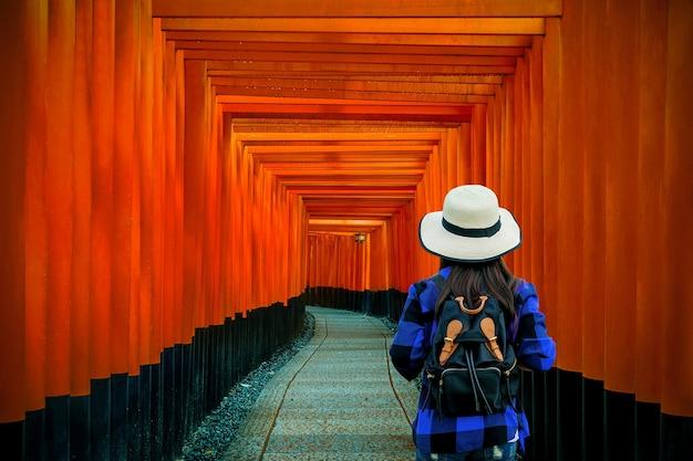 Femme Voyageur Avec Sac à Dos Au Sanctuaire Fushimi Inari Taisha à Kyoto, Au Japon. Photo gratuit