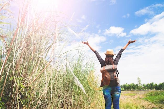 Femme voyageur se manoele et respire au champ de graminées et ciel bleu, concept de voyage errance, espace pour le texte Photo gratuit