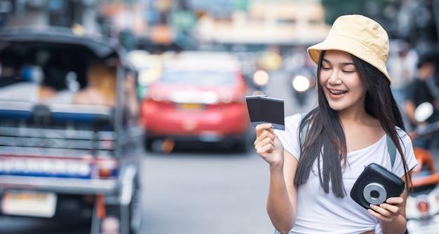 Femme de voyageur tenant une caméra instantanée et un film sur la route de khao san, ville de bangkok en thaïlande. Photo Premium