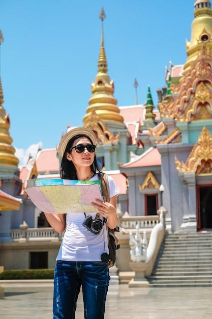 Femme voyageur en utilisant la carte locale et trouver le chemin pour aller à destination. Photo Premium