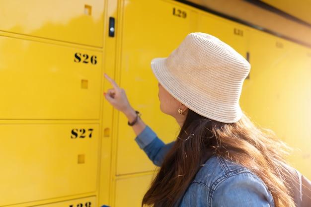 Femme Voyageur Utilisant Le Service De Casier Et Partir En Vacances En Ville. Photo Premium
