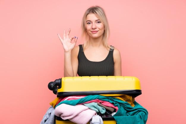 Femme De Voyageur Avec Une Valise Pleine De Vêtements Montrant Un Signe Ok Avec Les Doigts Photo Premium