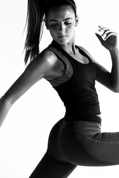 Femme vue de côté en costume de gym en niveaux de gris Photo gratuit