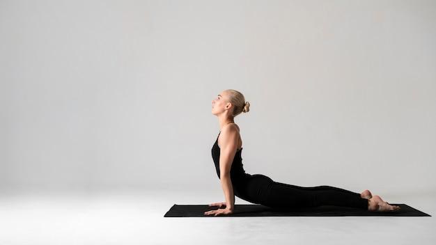 Femme vue de côté dans des vêtements noirs avec tapis de yoga Photo gratuit
