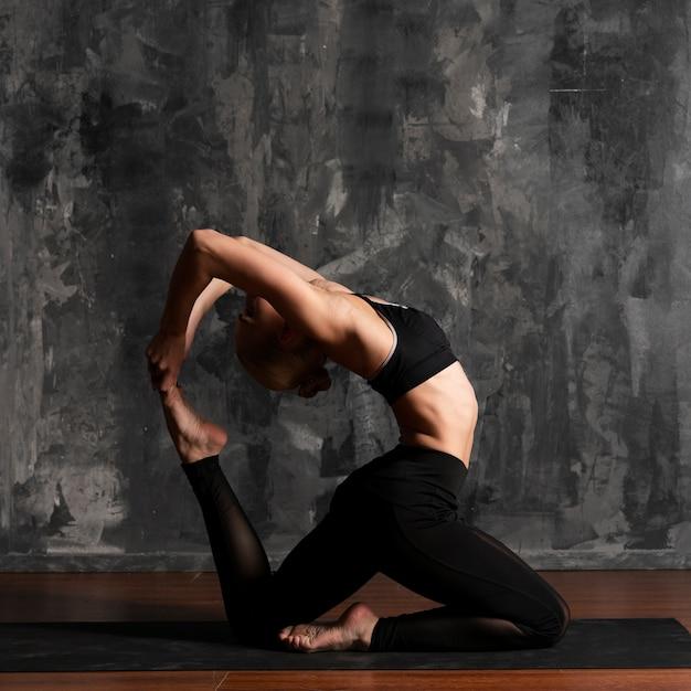 Femme vue de côté, faire du yoga avec fond de stuc Photo gratuit