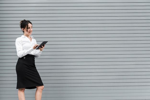 Femme vue de côté en regardant sa tablette Photo gratuit