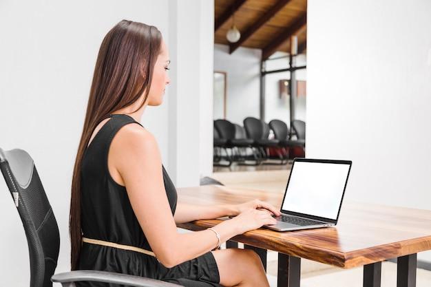 Femme vue de côté travaillant sur son ordinateur portable Photo gratuit
