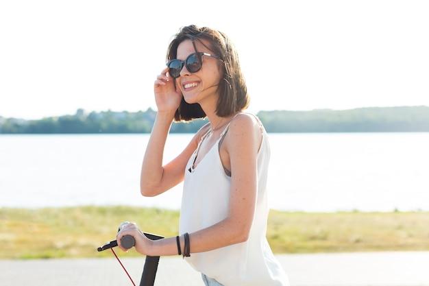 Femme vue côté trottinette Photo gratuit