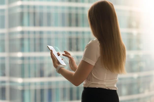 Femme vue de dos avec le doigt sur l'écran de la tablette Photo gratuit