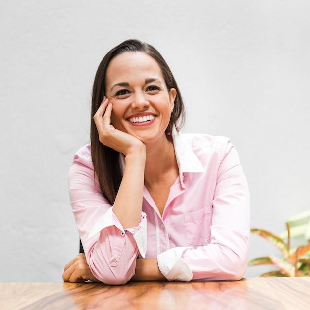 Femme vue de face, assise à son bureau Photo gratuit