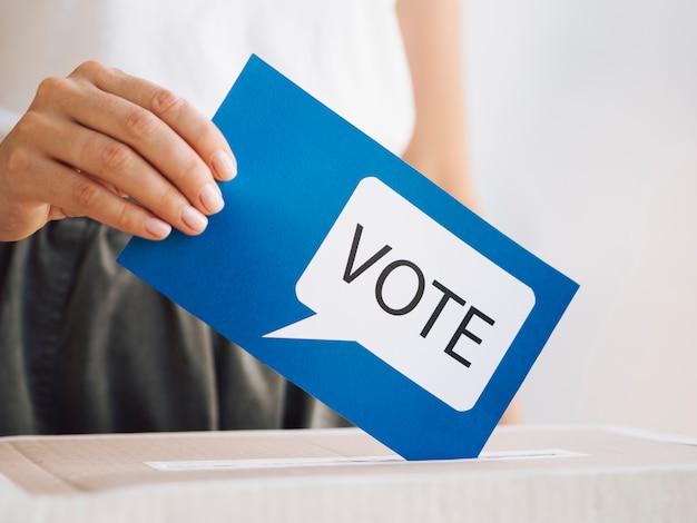 Femme vue de face mettant un message de vote dans une boîte de près Photo gratuit