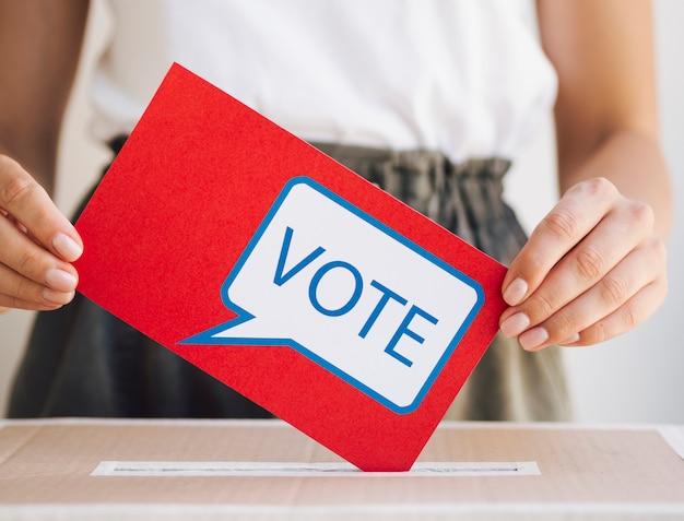 Femme vue de face mettant un message de vote dans une boîte Photo gratuit
