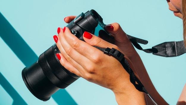 Femme Vue De Face Vérifiant Les Photos Sur L'appareil Photo Photo gratuit