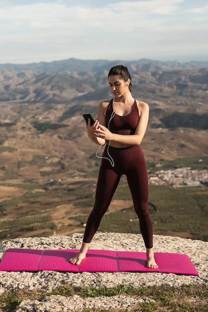 Femme, yoga, natte, vérification, téléphone Photo gratuit