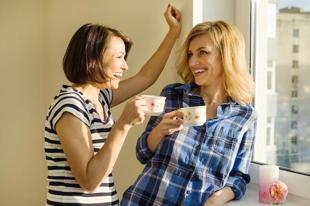 Les femmes adultes boivent du café, parlent, rient Photo Premium