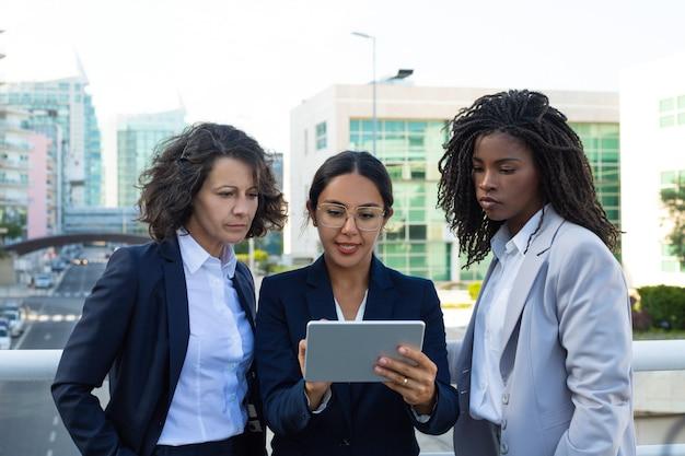 Femmes d'affaires concentrées avec tablette numérique Photo gratuit