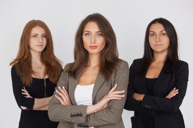 Femmes d'affaires modernes en costume avec leurs bras croisés debout sur fond gris. Photo Premium