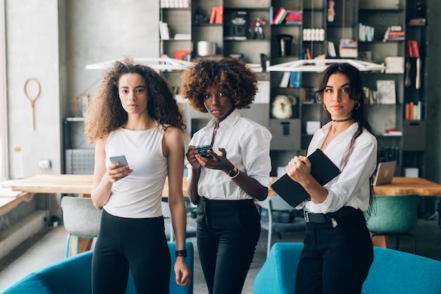 Femmes d'affaires multiculturelles debout avec appareil mobile dans un bureau de travail Photo Premium