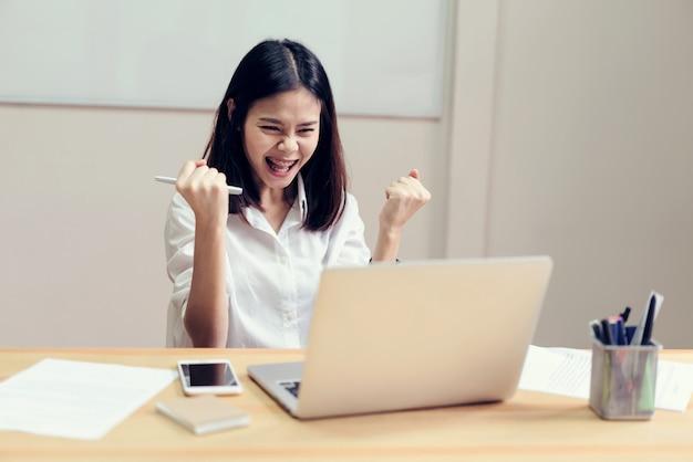Les femmes d'affaires sont heureuses de réussir dans leur travail et montrent un document sur la table en arrière-plan. Photo Premium